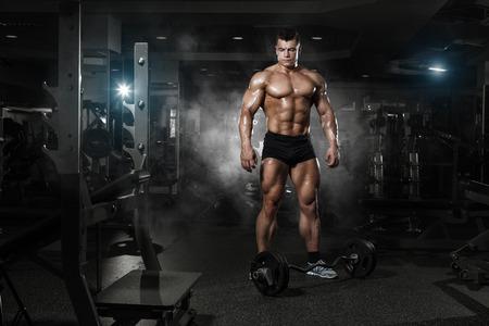 hombre fuerte: muy potencia atlética chico de pie con barra, ejercicio en el gimnasio