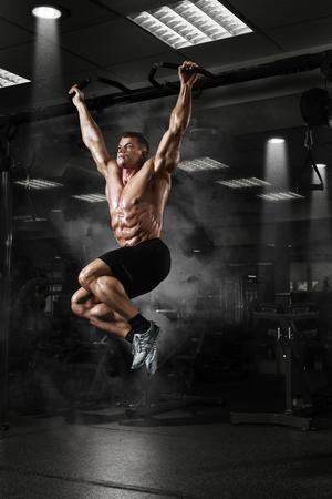 cuerpo hombre: Hombre del músculo atleta en el gimnasio haciendo elevaciones. Entrenamiento del Bodybuilder en gimnasia