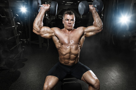 clenching: Athlete muscular bodybuilder in the gym training with dumbbells
