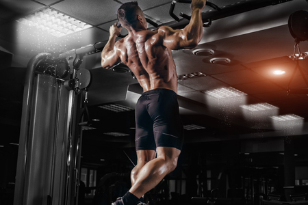 Muscle athlete man in gym making elevations. Bodybuilder training in gym