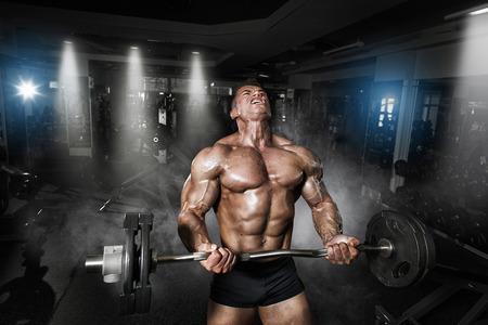 Atleet gespierde bodybuilder in de sportschool trainen met bar Stockfoto