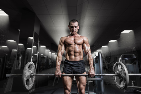 Muscular man workout with barbell at gym. Deadlift barbells workout. Brutal bodybuilder athletic man perfect abs, shoulders, biceps, triceps and chest.