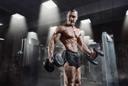 fitness hombres: poder guapo fisicoculturista atlética en la formación de bombeo de los músculos con pesas en el gimnasio. Músculos fuertes con una perfecta abs, hombros, bíceps, tríceps y pecho