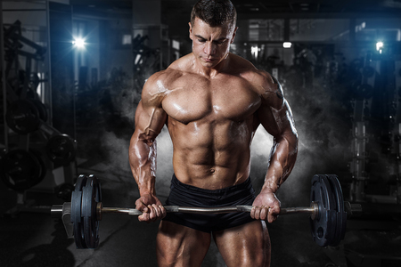 only the biceps: Athlete muscular bodybuilder in the gym training with bar