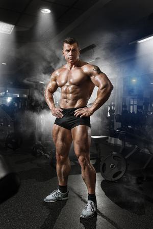 Portrait of a handsome muscular bodybuilder posing in gym