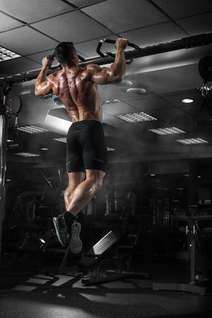 Hombre del músculo atleta en el gimnasio haciendo elevaciones. Entrenamiento del Bodybuilder en gimnasia Foto de archivo