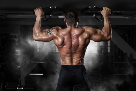 musculoso: Hombre del músculo atleta en el gimnasio haciendo elevaciones. Entrenamiento del Bodybuilder en gimnasia