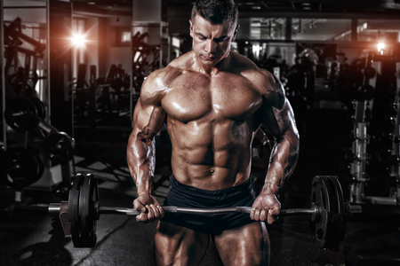 pectoral: Athlete muscular bodybuilder in the gym training with bar