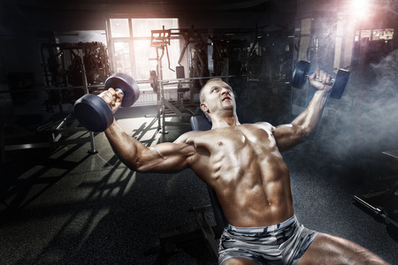 heavy weight: Athlete in the gym training with dumbbells Stock Photo