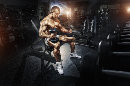 arm of a man: Athlete in the gym training with dumbbells Stock Photo