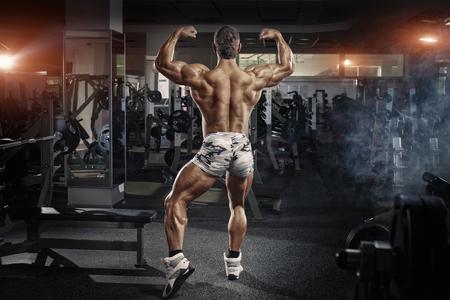 nude body: Bodybuilder man posing in the gym Stock Photo