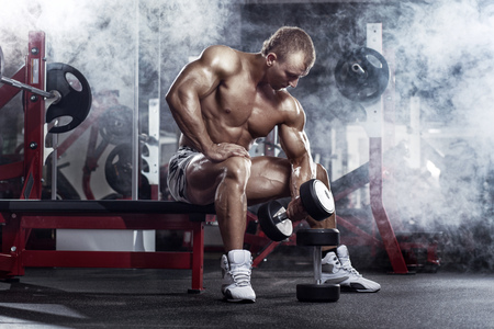 gym: very power athletic guy , execute exercise press with dumbbells, workout in sport hall