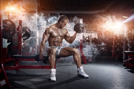 sixpack: very power athletic guy , execute exercise press with dumbbells, workout in the gym Stock Photo