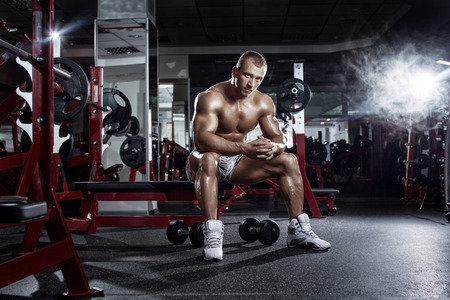 musculation: very power athletic guy, relaxing after workout in sport hall