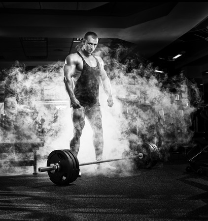 musculation: very power athletic guy standing with barbell, workout in the gym