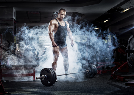 musculation: very power athletic guy standing with barbell, workout in sport hall in smoke