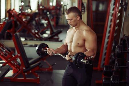 hombre fuerte: culturista hombre fuerte en un gimnasio de ejercicio con una mancuerna Foto de archivo