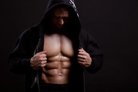Man met gespierde torso in hoodie op zwart toont zijn abs