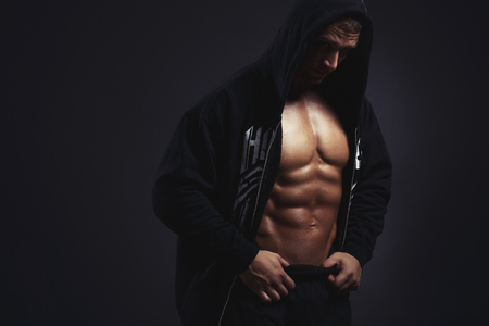 Man with muscular torso in hoodie on black Stock Photo