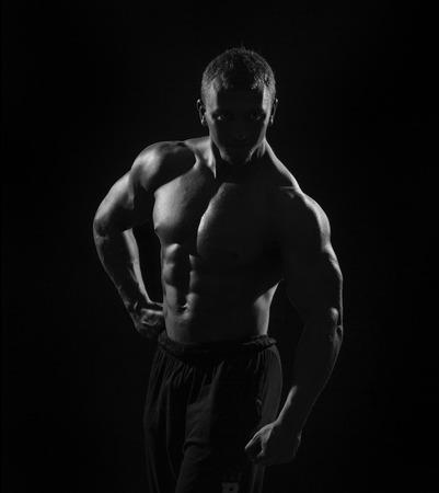 abdominal fitness: torso del hombre muscular con pesas sobre fondo negro en el estudio. Culturista elaboración de bíceps con mancuernas de bajo perfil