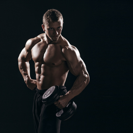 man working out: muscular torso man with dumbbell on black background in studio. Bodybuilder working out biceps with dumbbell low key