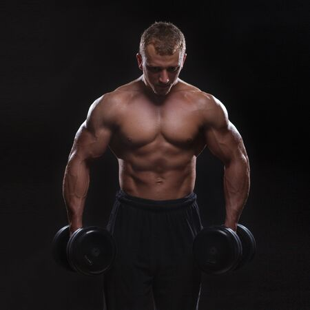 silueta hombre: torso del hombre muscular con pesas sobre fondo negro en el estudio. Culturista elaboración de bíceps con mancuernas de bajo perfil