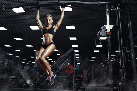 Sexy hot blonde fitness bikini girl with perfect shape body making elevations pull up in gym Standard-Bild