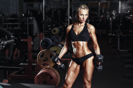 Sexy hot blonde fitness bikini girl with perfect shape body posing with dumbbells in gym