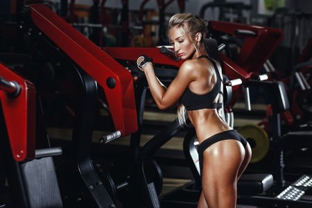 skimpy: Sexy hot blonde fitness bikini girl with perfect shape body and butt posing and relaxing in gym