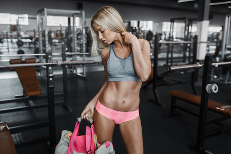 beauty and health: Athletic young sexy blonde girl prepares for exercising with bag in the gym