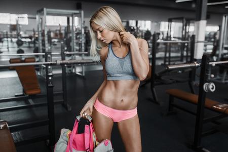 salud y deporte: Atlético muchacha rubia atractiva joven se prepara para hacer ejercicio con la bolsa en el gimnasio