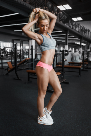 sexy girl posing: Athletic young sexy blonde girl with slim shape body posing in the gym