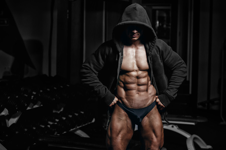 muscles: Athlete muscular bodybuilder posing in hoodie and shows his abs no face in the gym. Workout in gym Stock Photo