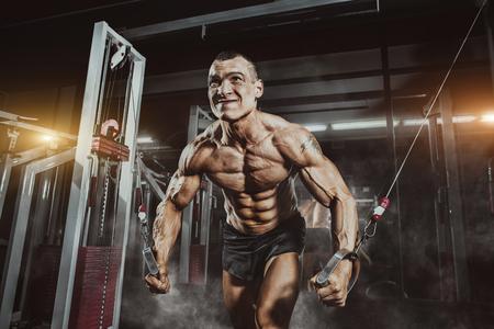 Athlete muscular bodybuilder training on simulator in the gym. Chest training in gym