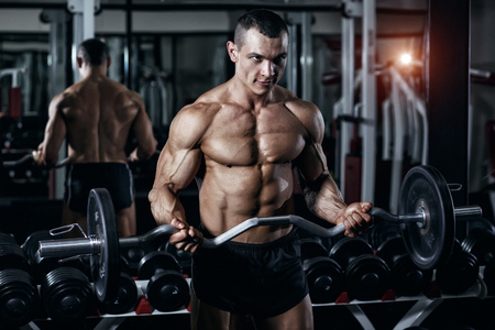 Athlete muscular bodybuilder training with barbell in gym. Biceps arms workout in gym