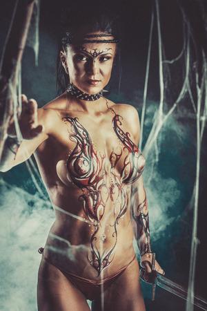 warrior: fantasía sexual de la mujer del guerrero con una espada en la atmósfera mística del antiguo bosque