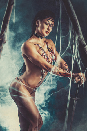 fantasy woman: Sexual fantasy woman warrior with a sword in the mystical atmosphere of the old forest
