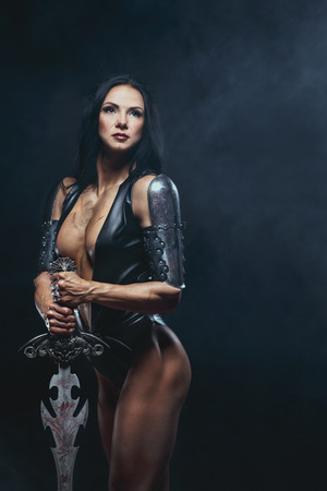 young woman nude: Sexy Fantasy Warrior Woman with big sword on black Stock Photo