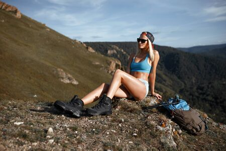 see: Tourist woman mountain hiker siting on background mountain