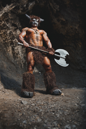 rampage: The bodyart man angry minotaur greek with axe in cave Stock Photo
