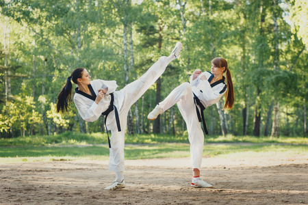 battle: Two karate woman fighting on outdoor