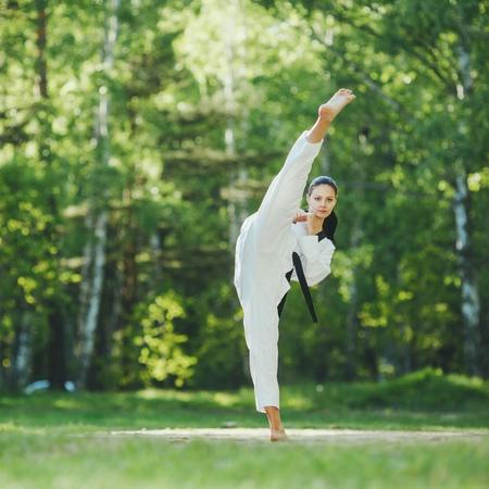 Karate girl with black belt high kick outdoor training Stock Photo