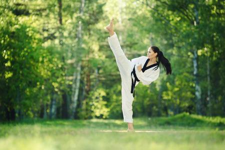 patada: muchacha del karate con cinturón negro remate alto entrenamiento al aire libre Foto de archivo