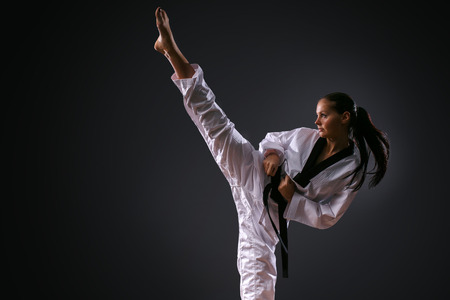 Karate girl with black belt high kick on black background studio shot