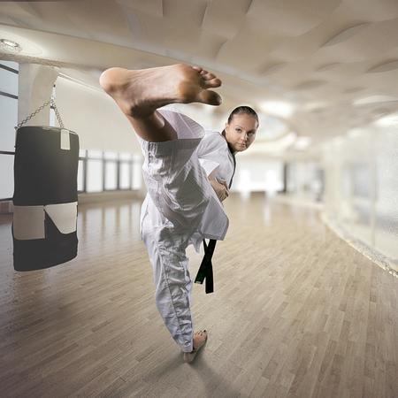 girl kick: Karate girl with black belt high kick indoor martial arts practice training Stock Photo