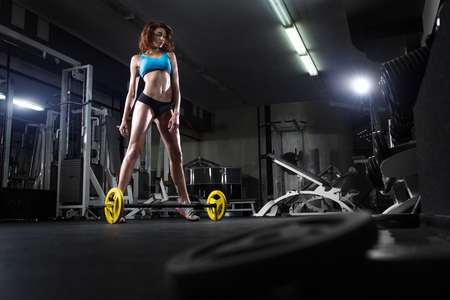 fitness training: fitness brunette sexy girl prepares for training with barbell in gym Stock Photo