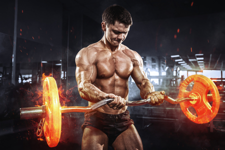 Muscular athlete bodybuilder with burning barbell concept in gym Banco de Imagens