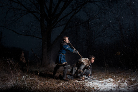 The battle between medieval knights in the style of Game of Thrones in winter forest landscapes. A warrior with a spear kills swordtail Stock Photo