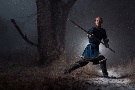 longsword: Medieval knight with sword in armor as style Game of Thrones in Winter Forest Landscapes Stock Photo