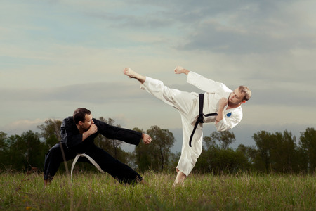 Karate fighters practice outdoor. Men in white and black kimono fighting on the grass